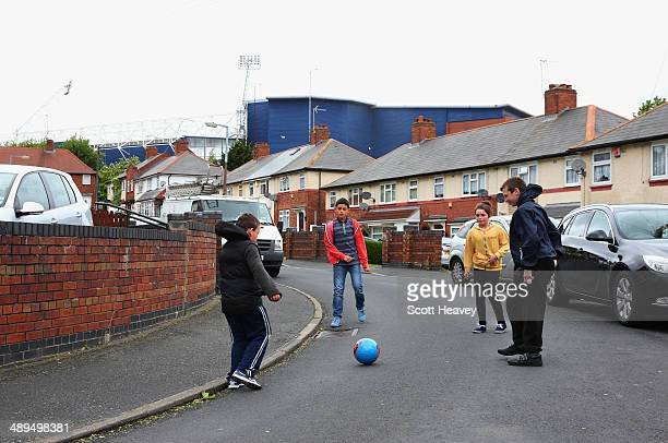 Children play football in the street prior to the Barclays Premier League match between West Bromwich Albion and Stoke City at The Hawthorns on May...