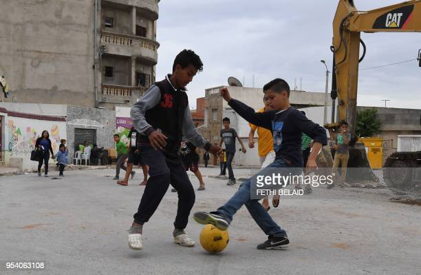 Children play football in the streets of Ettadhamen city on April 30 a popular and poor region of Greater Tunis At the approach of the first...