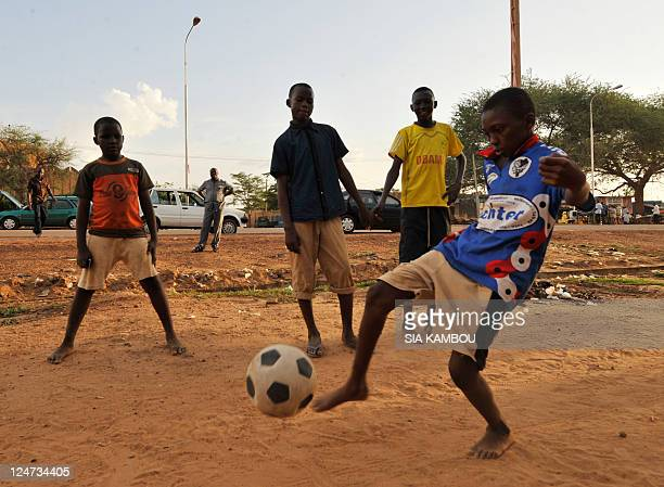 Children play football in the streets of Harovanda a lower class neighborhood of Niamey on September 11 2012 AFP PHOTO / SIA KAMBOU