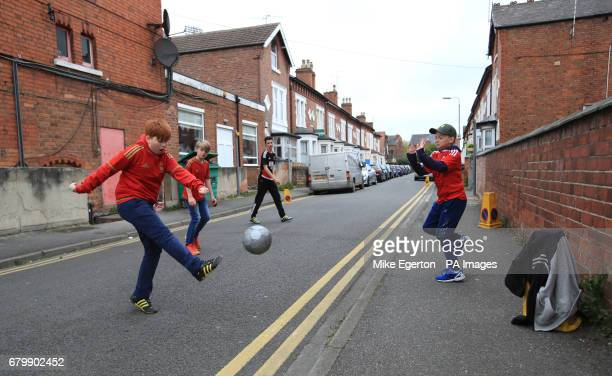 Children play football in the streets outside The City Ground before the Sky Bet Championship match at the City Ground Nottingham