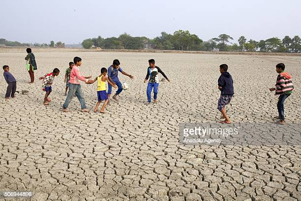 Children play football on deep cracks field as rise of sealevel causes deep cracks by leaving salt on ground after evaporation in Satkhira Bangladesh...