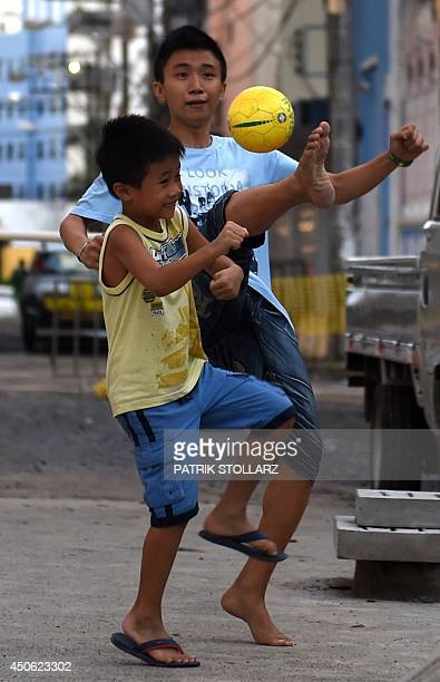 Children play football on the streets of Salvador on June 14 during the 2014 FIFA World Cup football tournament AFP PHOTO / PATRIK STOLLARZ