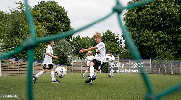 "Children play football on the synthetic turf football ground of the ""Georg Buechner Schule"" on May 16, 2007 in Darmstadt, Germany. The German..."