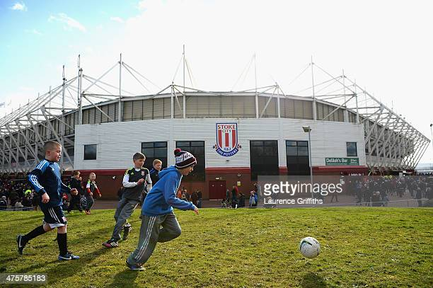 Children play football outside the stadium prior to the Barclays Premier League match between Stoke City and Arsenal at Britannia Stadium on March 1...