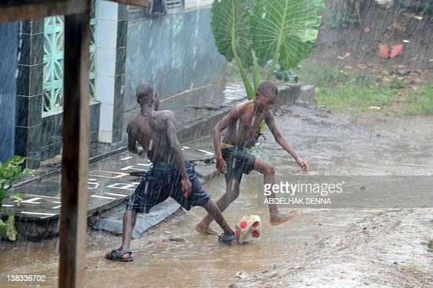 Children play football under the rain in a street of Bata on February 6 2012 AFP / PHOTO / ABDELHAK SENNA