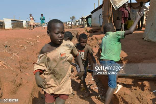 Children play in a drainage ditch in the Protection of Civilians site in Wau on February 1, 2020. - 13,000 civilians shelter under UN protection at...