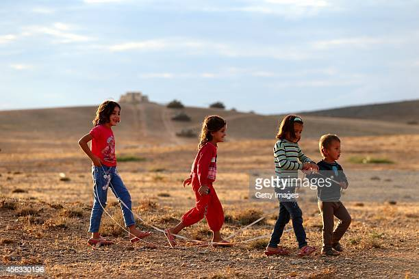Children play in a field as Turkish Armed Forces dispatch tanks to the Turkish Syrian border as clashes intensified with Islamic State of Iraq and...