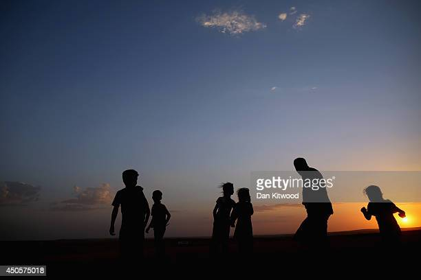 Children play in a field at sunset next to a temporary displacement camp set up next to a Kurdish checkpoint on June 13 2014 in Kalak Iraq Thousands...