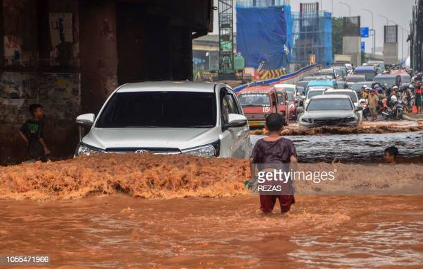 Children play in a flooded road as vehicles move through floodwaters in Bekasi West Java province on October 30 following heavy onsoon rains in the...