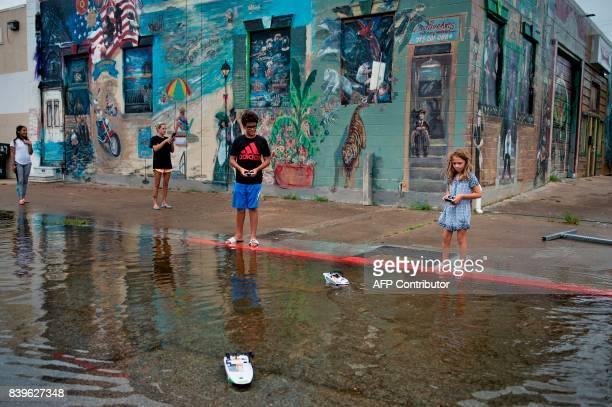 Children play in a flooded road following the passage of Hurricane Harvey on August 26, 2017 in Galveston, Texas. / AFP PHOTO / Brendan Smialowski