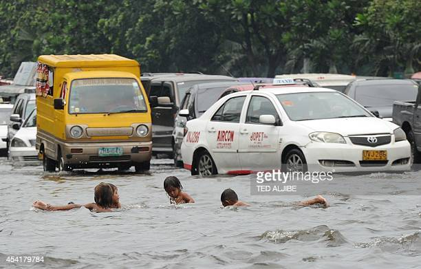 Children play in a flooded street caused by heavy rains overnight while motorists drive past in Manila on August 26 2014 The weather bureau issued a...