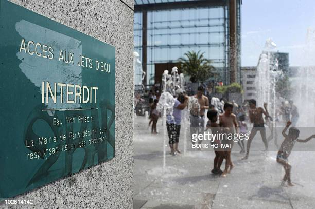 Children play in a fountain despite of the board reading that the access is forbidden on July 11, 2010 in Paris while enjoying the warm weather at...