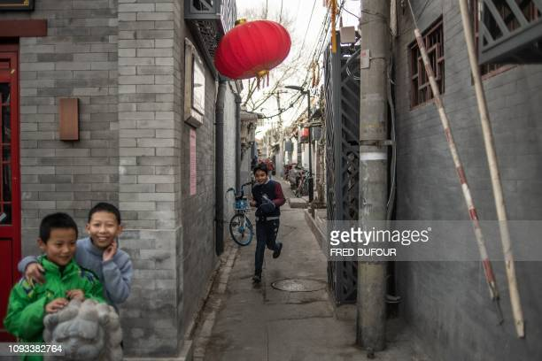 TOPSHOT Children play in a 'Hutong' traditional Beijing courtyards ahead of the upcoming Lunar New Year in Beijing on February 3 2019 Millions of...
