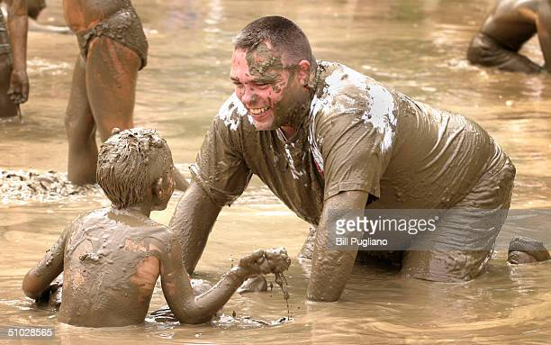 Children play in a lake of mud during the annual Mud Day event July 6 2004 in Westland Michigan The popular annual event brings together several...