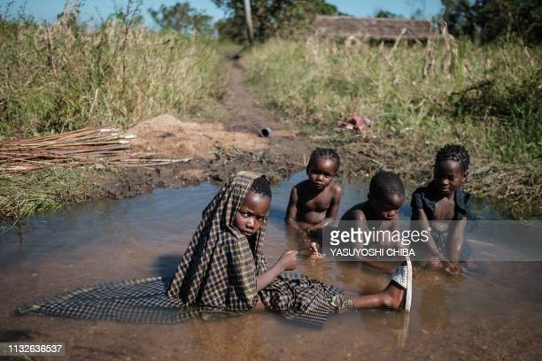 Children play in a new stream created by flooded water after the passage of the cyclone Idai in Tica Mozambique on March 24 2019 Cyclone Idai smashed...