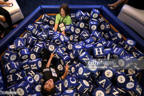 Children play in a pen filled with foam cubes outside the Scripps National Spelling Bee at the Gaylord National Resort & Convention Center May 28,...