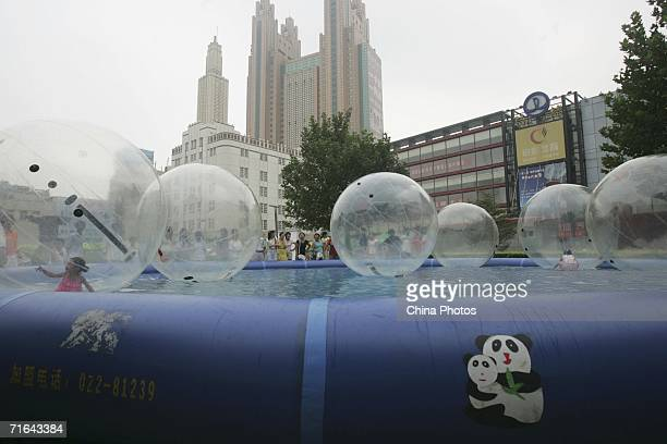 Children play in a water walking ball at a square on August 13 2006 in downtown Tianjin Municipality a megacity neighbouring Beijing China The...