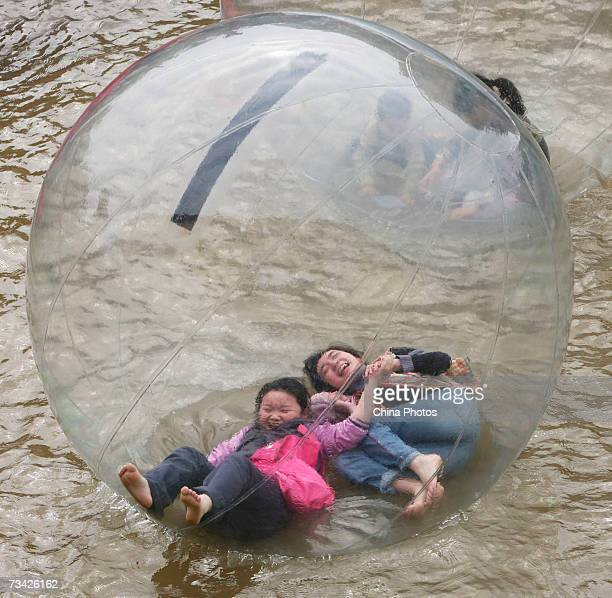 Children play in a water walking ball at the Foreigners Street on February 26 2007 in Chongqing Municipality China The tourist site received almost...