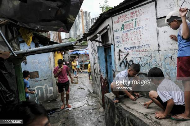 Children play in an alleyway in the San Roque neighborhood as commercial high-rise buildings stand in the background in Quezon City, Metro Manila,...