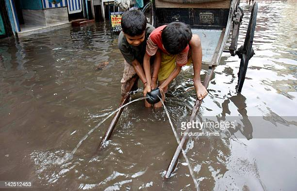 Children play in flood waters due to heavy rain on Amherst Street on April 6 2012 in Kolkata India The MET department predicts more rainfall through...