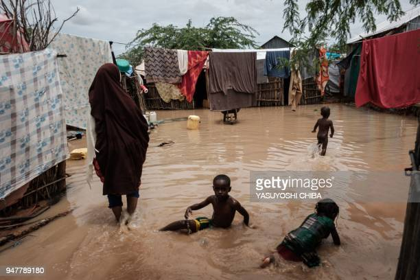 Children play in floodwaters after a heavy rainy season downpour as they seek to fill sandbags at the Dadaab refugee complex, in the north-east of...