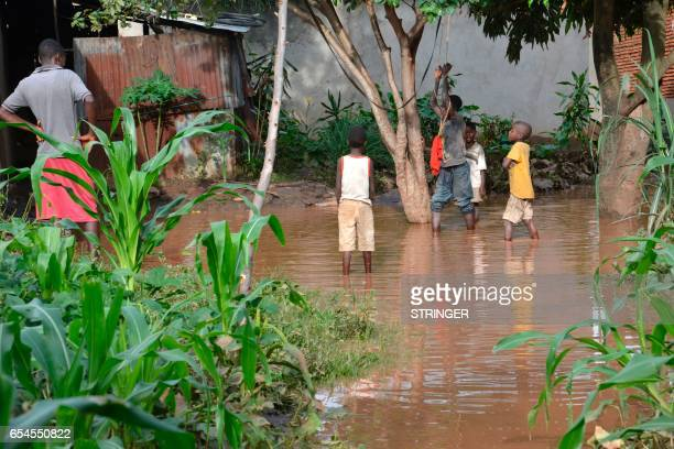 Children play in floodwaters after latrines overflow in Buterere, northwest of Bujumbura, on March 17 after overnight torrential rains destroyed more...