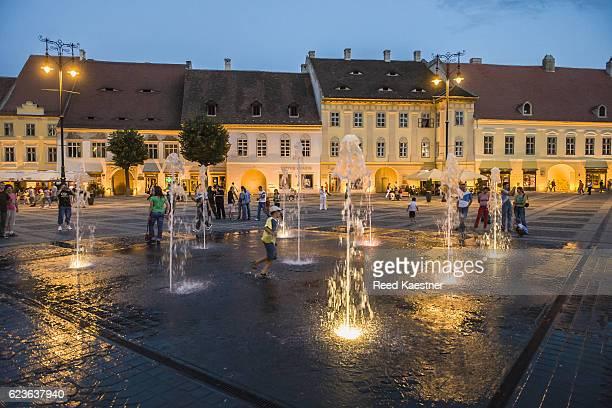 Children play in fountains at twilight in the Grand Square Sibiu, Romania