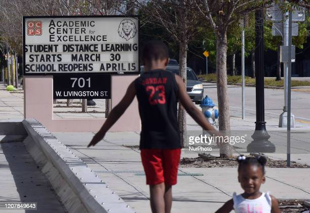 Children play in front of a school in Orlando Florida on March 20 2020 that was closed due to the coronavirus but will begin distance learning on...