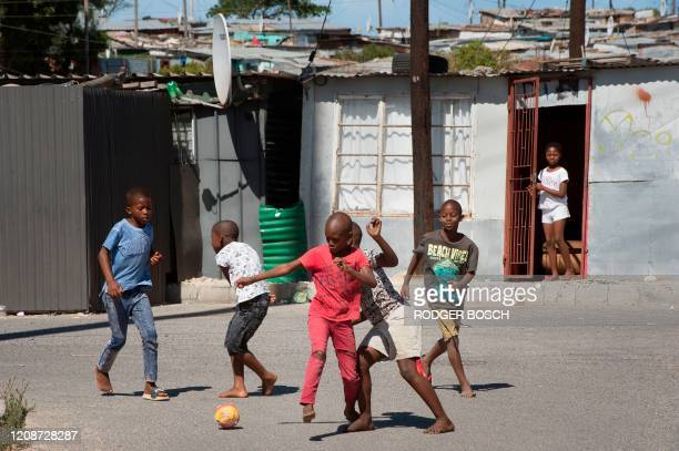 Children play in front of shacks in Khayelitsha, near Cape Town, on March 31, 2020 in Cape Town. - Local government administrators in Cape Town said...