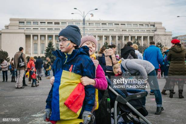 Children play in front of the government headquarters in Bucharest on February 4 where families gathered to protest against the controversial decrees...