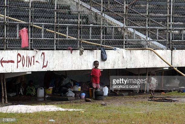 Children play in front of the Samuel Kanyon Doe stadium stands under which their Liberian family displaced by war took shelter 14 July 2003 in...