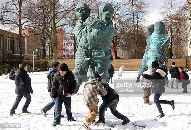 Children play in front of the sculpture United Enemies by Thomas Schuette in the garden of the Berggruen Museum on March 15 2013 in Berlin Germany...