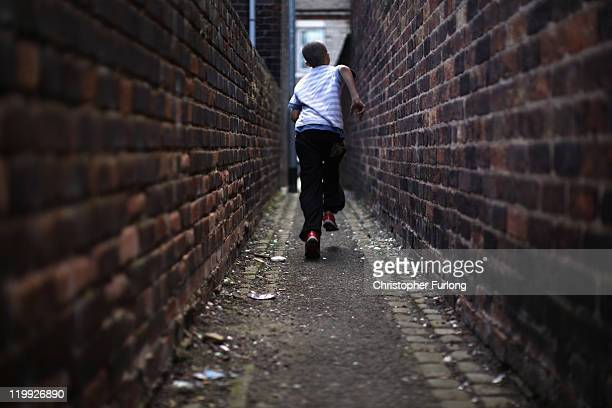 Children play in the back alleys and streets of Summerbank in Tunstall as the school Summer holidays begin on July 26, 2011 in Stoke on Trent,...