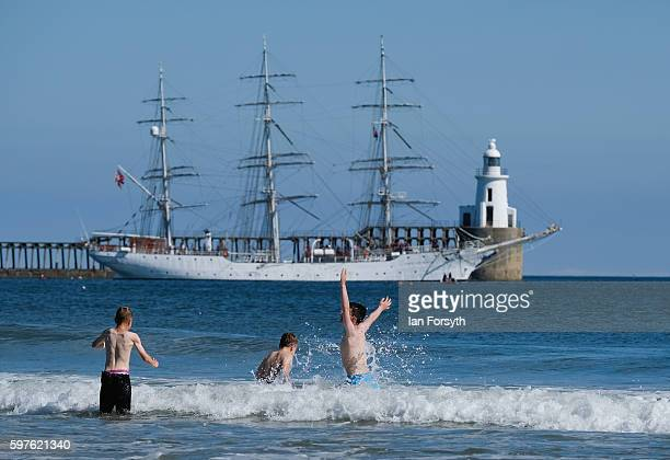 Children play in the beachbreak as the Polish ship Dar Mlodziezy leaves Blyth harbour during the North Sea Tall Ships Parade of Sail on August 29...