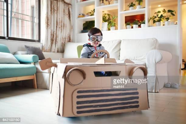 Los niños juegan en el coche de cartón