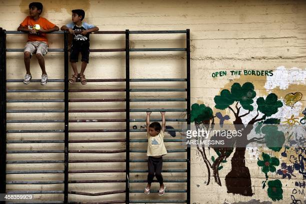 Children play in the courtyard of an abandoned school used by volunteers for hosting Syrian and Afghan refugees in Athens on July 1, 2016. Some 250...