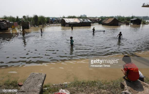 Children play in the flooded waters of River Yamuna against a backdrop of submerged houses along the banks of the river near Kashmere Gate ISBT on...