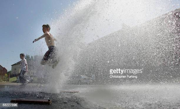 Children play in the fountain of water created by an opened fire hydrant in the East End of Glasgow on July 12 Glasgow Scotland Temperatures climbed...