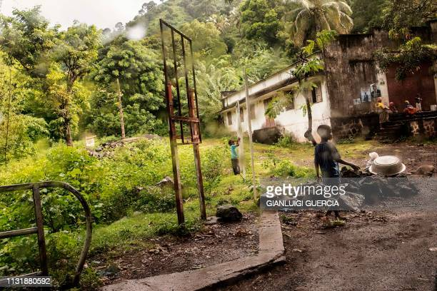 Children play in the front yard of a warehouse as rain falls down on March 21 on the outskirts of Mutsamudu the capital of Anjouan Island Comoros...