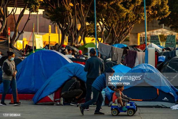 Children play in the makeshift shelter camps for Central American migrants while awaiting the US authorities to allow them to enter to begin their...