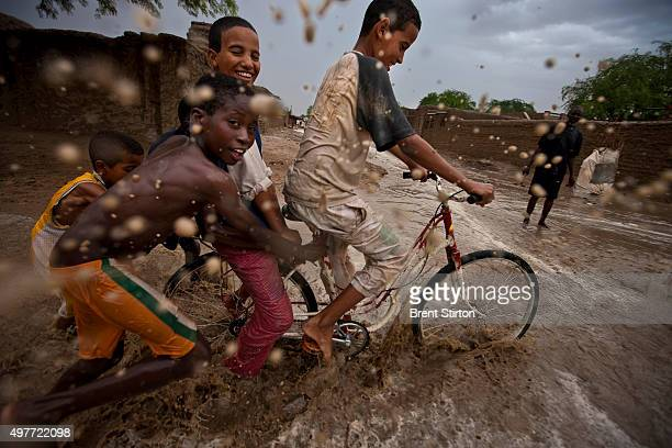 Children play in the rain in a welcome respite from the desert heat in a street scene in a long established centre of learning for Africa on...