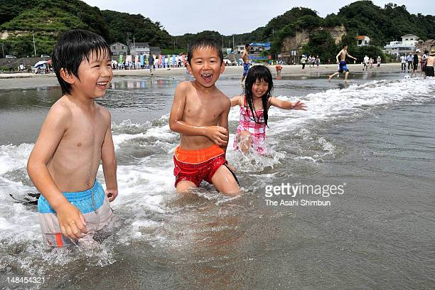 Children play in the sea at Nakoso Beach opens for the first time after the Fukushima Daiichi Nuclear Power Plant accident on July 16 2012 in Iwaki...