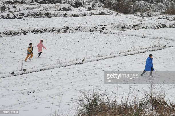 Children play in the snow in Shaoguan south China's Guangdong province on January 24 2016 Much of China shivered as a teethchattering cold snap broke...