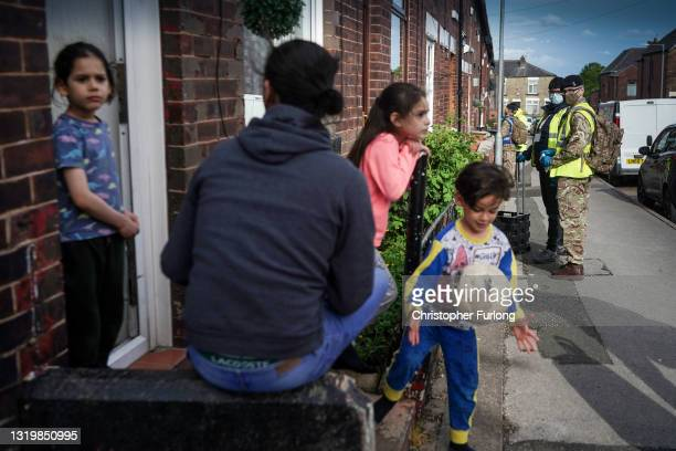 Children play in the street as gunners from the Royal Horse Artillery distribute Covid-19 polymerase chain reaction tests to local residents on May...