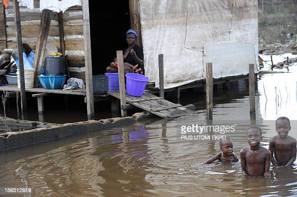 Children play in the water next to a flooded house in the town of Yenagoa in the Bayelsa oilrich Niger Delta region on November 15 2012 Nigeria...