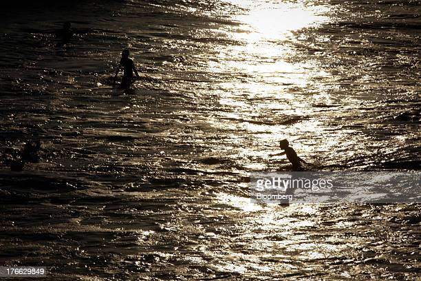 Children play in the waves in the Pacific Ocean north of the Santa Monica Pier in Santa Monica California US on Monday Aug 5 2013 Overall US...