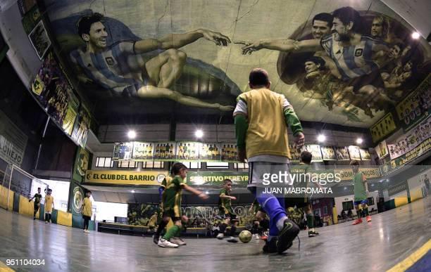Children play indoor football at Sportivo Pereyra de Barracas football club in Buenos Aires on April 24 where local artist Santiago Barbeito created...