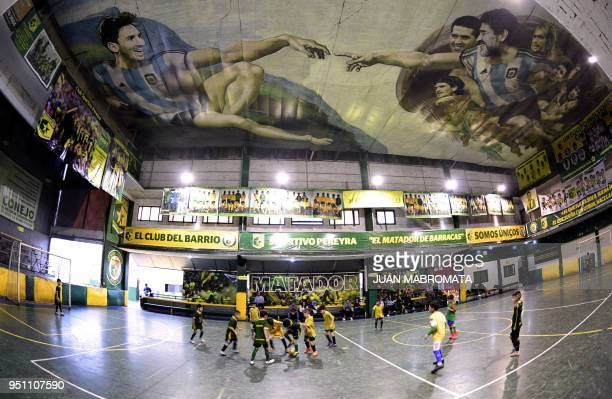 Children play indoor football at Sportivo Pereyra de Barracas football club in Buenos Aires on April 24 where local artist Santiago Barbeito created...