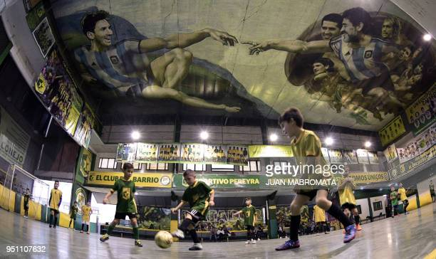 TOPSHOT Children play indoor football at Sportivo Pereyra de Barracas football club in Buenos Aires on April 24 where local artist Santiago Barbeito...