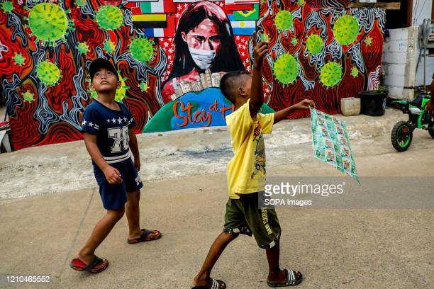 Children play kites near a coronavirus awareness graffiti during a lockdown. Indonesian local artists drew murals on the walls of the houses for the...